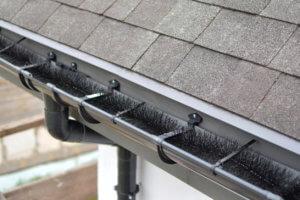 Plastic guard brush in new dark grey plastic rain gutter on asphalt shingles roof.